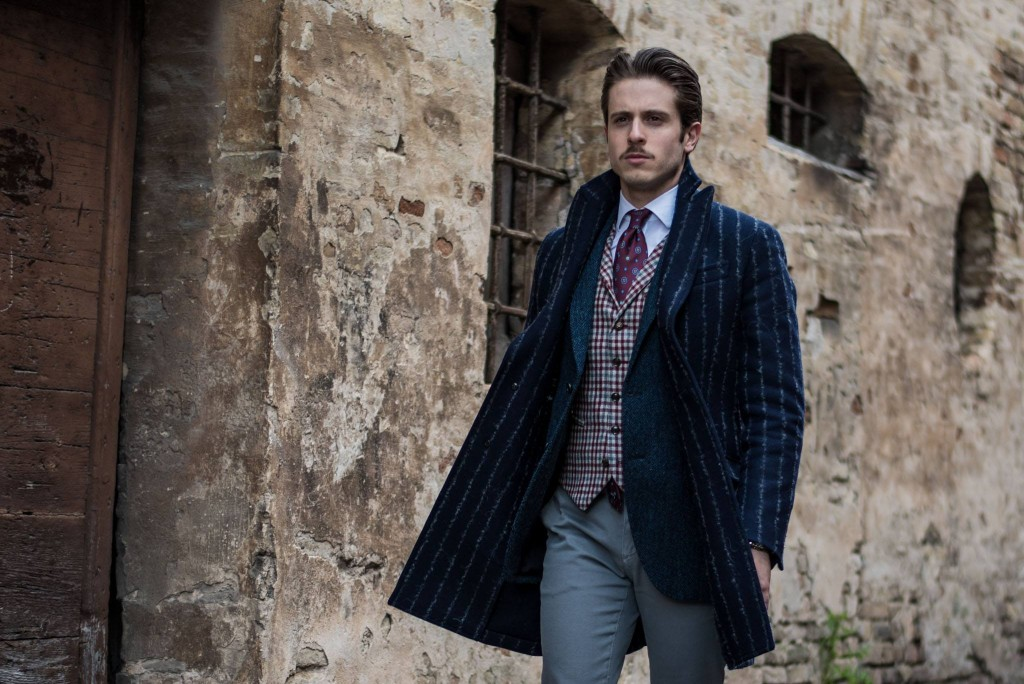 The ice colored trousers by Yan Simmon match the gray and burgundy checkered waist coat, presented here with a blue herringbone jacket. The blue coat by Hevò is made of wool and pinstriped fabric